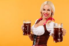 Young sexy Oktoberfest girl - waitress, wearing a traditional Bavarian dress, serving big beer mugs on orange background Royalty Free Stock Images