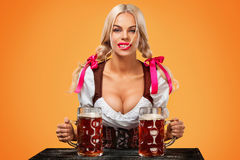 Young sexy Oktoberfest girl - waitress, wearing a traditional Bavarian dress, serving big beer mugs on orange background Stock Photos