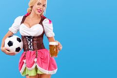 Young sexy Oktoberfest girl - waitress, wearing a traditional Bavarian dress, serving big beer mugs and taking soccer Stock Photos