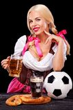 Young sexy Oktoberfest girl - waitress, wearing a traditional Bavarian dress, serving big beer mugs and taking soccer Stock Photo