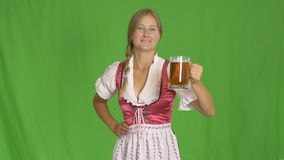 Young sexy Oktoberfest waitress, wearing a traditional Bavarian dress, serving big beer mug on green background stock video