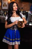 Young Oktoberfest waitress, wearing a traditional Bavarian dress, serving big beer mug Stock Images