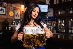 Young sexy Oktoberfest waitress, wearing a traditional Bavarian dress, serving big beer mugs at bar. Stock Photography