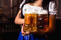Young sexy Oktoberfest waitress, wearing a traditional Bavarian dress, serving big beer mugs at bar. Royalty Free Stock Photos