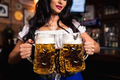Young Oktoberfest waitress, wearing a traditional Bavarian dress, serving big beer mugs at bar. Stock Photos