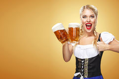 Young sexy Oktoberfest waitress, wearing a traditional Bavarian dress, serving big beer mugs on blue background with Stock Images