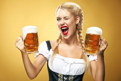 Young sexy Oktoberfest waitress, wearing a traditional Bavarian dress, serving big beer mugs on blue background. Royalty Free Stock Photography