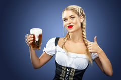 Young Oktoberfest waitress, wearing a traditional Bavarian dress, serving big beer mugs on blue background. Royalty Free Stock Image