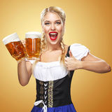 Young Oktoberfest waitress, wearing a traditional Bavarian dress, serving big beer mugs on blue background Royalty Free Stock Photo