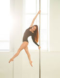 Young sexy pole dance woman. Bright white colors. Royalty Free Stock Image