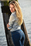 Young pretty woman standing on the pier near the sea marina. Stock Photography