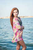 Young sexy red hair girl in multicolored blouse posing on the beach. Sensual attractive woman with long hair, summer shot at sea Royalty Free Stock Photography