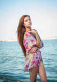 Young sexy red hair girl in multicolored blouse posing on the beach. Sensual attractive woman with long hair, summer shot at sea Royalty Free Stock Images