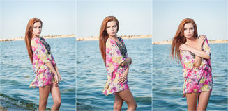 Young sexy red hair girl in multicolored blouse posing on the beach. Sensual attractive woman with long hair, summer shot at sea Stock Photography