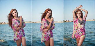 Young sexy red hair girl in multicolored blouse posing on the beach. Sensual attractive woman with long hair, summer shot at sea Stock Images