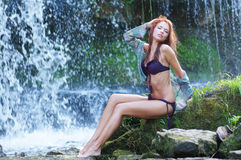 A young and sexy redhead posing near the waterfall Royalty Free Stock Photos