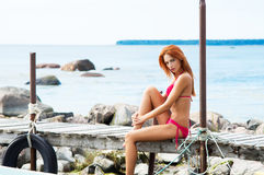 Young and sexy redhead woman relaxing on the pier Stock Image