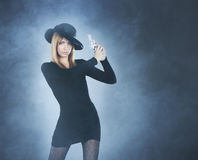 A young and redhead woman with a silver pistol Royalty Free Stock Photography