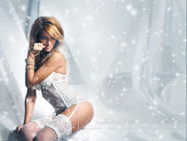 Young and sexy redhead woman in white lingerie on the snow Royalty Free Stock Photography