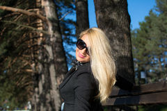 Young russian girl in a park with long blond hair. Young attractive business woman with long blonde hair in a park royalty free stock photo