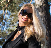 Young russian girl in a park with long blond hair. Young attractive business woman with long blonde hair in a park royalty free stock photos