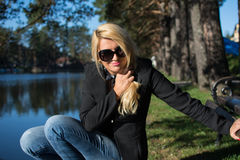 Young russian girl in a park with long blond hair. Young attractive woman with long blonde hair in a park royalty free stock image