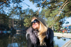.Young russian girl in a park with long blond hair. Young attractive woman with long blonde hair in a park stock photo
