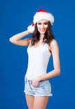 Young and sexy Santa girl in a Christmas hat. Young and sexy Santa girl in Christmas hat over blue background Royalty Free Stock Photography