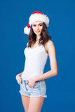 Young and sexy Santa girl in a Christmas hat. Young and sexy Santa girl in Christmas hat over blue background Royalty Free Stock Image