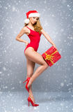 Young and Santa girl in a red Christmas swimsuit Stock Photos