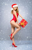 Young and Santa girl in a red Christmas swimsuit Stock Images