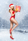 Young and sexy Santa girl in a red swimsuit with a present Stock Photo