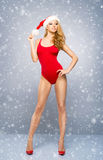 Young and sexy Santa girl in a red swimsuit on a snowy background Stock Photography