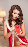 Young sexy Santa holding a gift, boudoir shoot. Attractive brunette with long hair wearing a provocative lingerie Xmas style Royalty Free Stock Photography