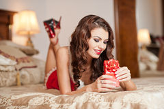 Young sexy Santa holding a gift, boudoir shoot. Attractive brunette with long hair wearing a provocative lingerie Xmas style Royalty Free Stock Images