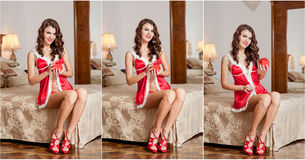 Young sexy Santa holding a gift, boudoir shoot. Attractive brunette with long hair wearing a provocative lingerie Xmas style Royalty Free Stock Photos