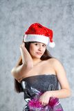Young sexy Santa indress  on grey Royalty Free Stock Images