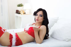 Young sexy santa lying on bed Stock Photos
