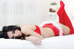 Young sexy santa lying on bed Royalty Free Stock Images