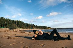 Young sensual couple laying and hugging on sand at the beach. Passion between two lovers. Sex and love on the beach. Cold autumn weather, coastline, park and royalty free stock image