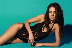 Sexy tanned girl in black swimsuit. Young sexy slim tanned woman in black swimsuit posing and lying on blue background. Fashion portrait of beautiful girl with Royalty Free Stock Image