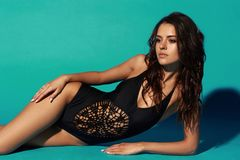 Sexy tanned girl in black swimsuit. Young sexy slim tanned woman in black swimsuit posing and lying on blue background. Fashion portrait of beautiful girl with Royalty Free Stock Images