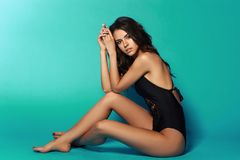 Sexy tanned girl in black swimsuit. Young sexy slim tanned woman in black swimsuit posing and sitting on blue background. Fashion portrait of beautiful girl with Stock Photos