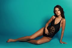 Sexy tanned girl in black swimsuit. Young sexy slim tanned woman in black swimsuit posing and sitting on blue background. Fashion portrait of beautiful girl with Royalty Free Stock Photo