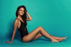 Sexy tanned girl in black swimsuit. Young sexy slim tanned woman in black swimsuit posing and sitting on blue background. Fashion portrait of beautiful girl with Stock Photo