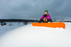 Young snowboarder sitting on mountainside Stock Photos