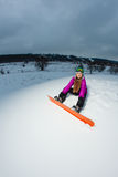 Young snowboarder sitting on mountainside Stock Images