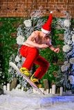 Young sporty young man in red pants and santa hat jumping with a snowboard royalty free stock photos