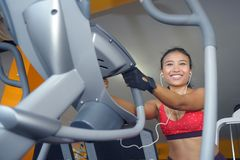 and sweaty Asian woman training hard at gym using elliptical pedaling machine gear in intense workout Royalty Free Stock Image