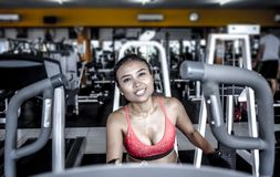 and sweaty Asian woman training hard at gym using elliptical pedaling machine gear in intense workout Stock Photo